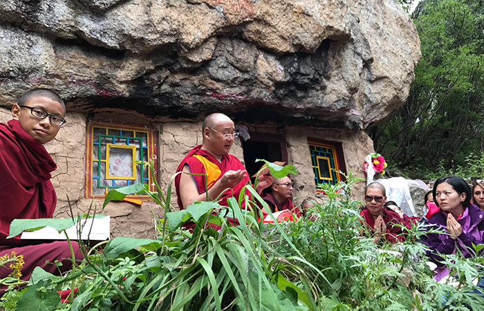 The 7th Dzogchen Rinpoche giving teachings on The Words of My Perfect Teacher which was written in the cave in the picture, above Dzogchen monastery